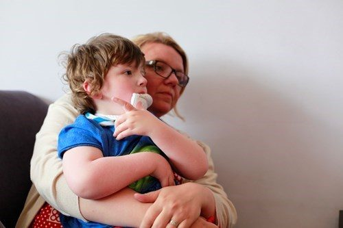 Images shows a young boy sat on his mums lap.