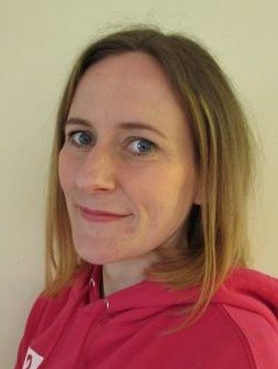 Headshot of Rachael wearing a pink hoodie