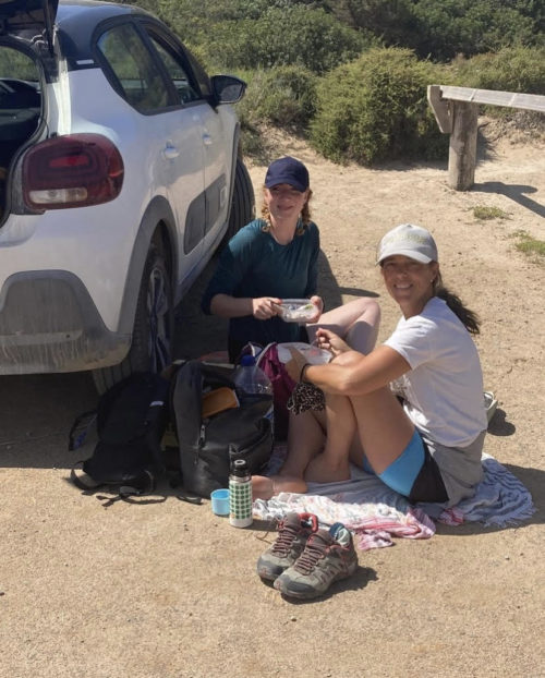 Two girls sit in shorts and t shirts, wearing caps,with a packed lunch by a white car on a hot day in Ibiza